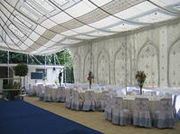 A marquee with tables and blue carpet set up in Sandhurst for a Wedding event